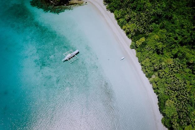 Widok z lotu ptaka na piękną rajską lagunę i białą piaszczystą plażę. lokalne łodzie na powierzchni. koncepcja letnich wakacji egzotycznych.