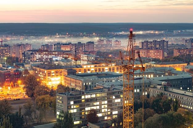 Widok z lotu ptaka na piękne, płonące światła wieczornego miasta pogrążonego we mgle z wieżowcami i placem budowy