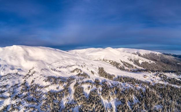 Widok z lotu ptaka na piękne zimowe stoki górskie pokryte śniegiem i lasem jodłowym w słoneczny bezchmurny dzień