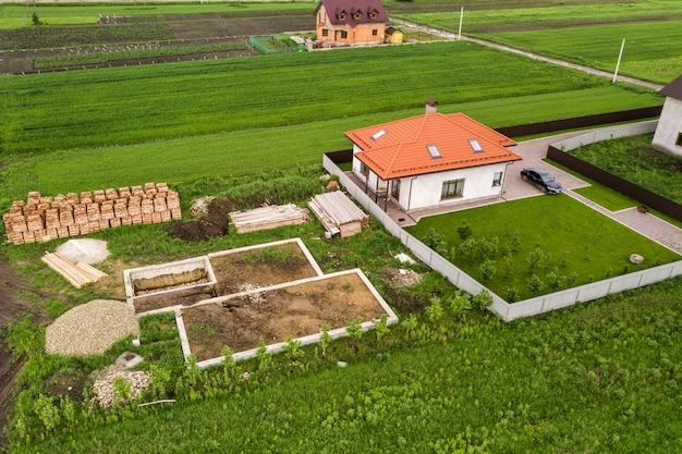 Widok z lotu ptaka na plac budowy przyszłego domu murowanego, betonowa podłoga fundamentowa i stosy żółtych cegieł glinianych do budowy.