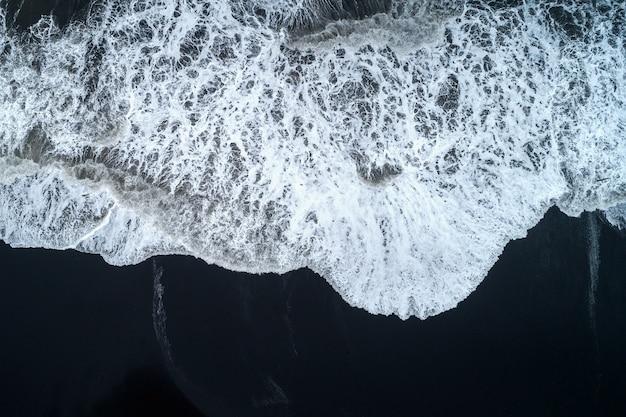 Widok z lotu ptaka na plażę z czarnym piaskiem i fale oceanu w islandii.