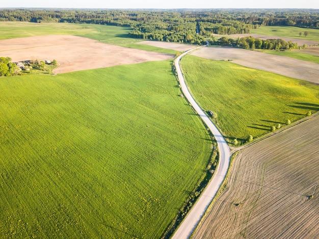 Widok z lotu ptaka na polną drogę oddzielającą zielone łąki i brązowe pola uprawne