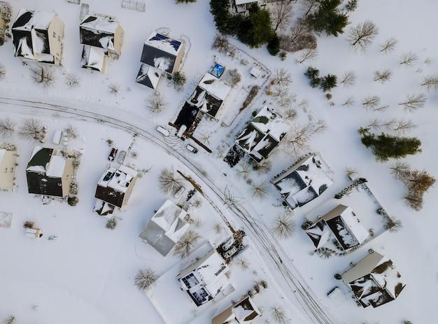 Widok z lotu ptaka na prywatne domy w okresie zimowym na pokrytych śniegiem tradycyjnych przedmieściach mieszkaniowych