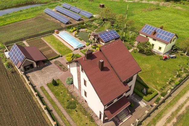 Widok z lotu ptaka na prywatny dom w lecie z niebieskimi słonecznymi panelami fotowoltaicznymi na dachu i na podwórku.