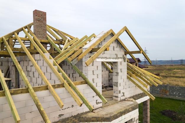 Widok z lotu ptaka na prywatny dom z ceglanymi ścianami z betonu komórkowego i drewnianą ramą na przyszły dach.