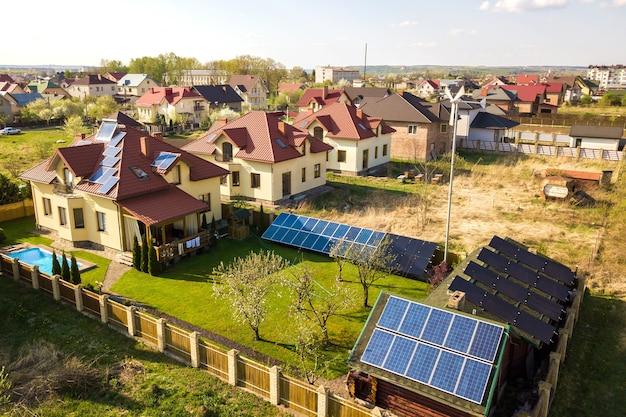 Widok z lotu ptaka na prywatny dom z podwórkiem pokrytym zieloną trawą, panelami słonecznymi na dachu, basenem z niebieską wodą i generatorem turbiny wiatrowej.
