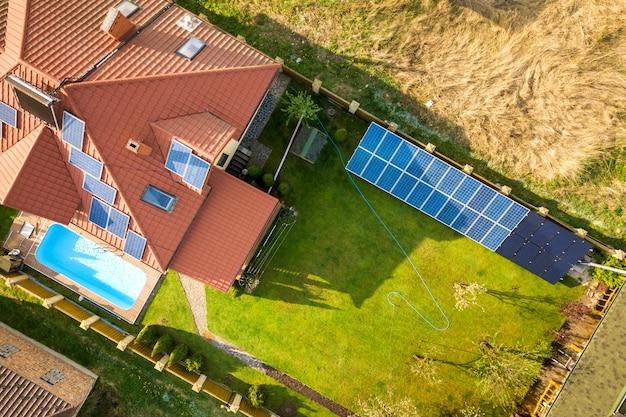 Widok z lotu ptaka na prywatny dom z zieloną trawą, podwórkiem, panelami słonecznymi na dachu, basenem i generatorem turbin wiatrowych.