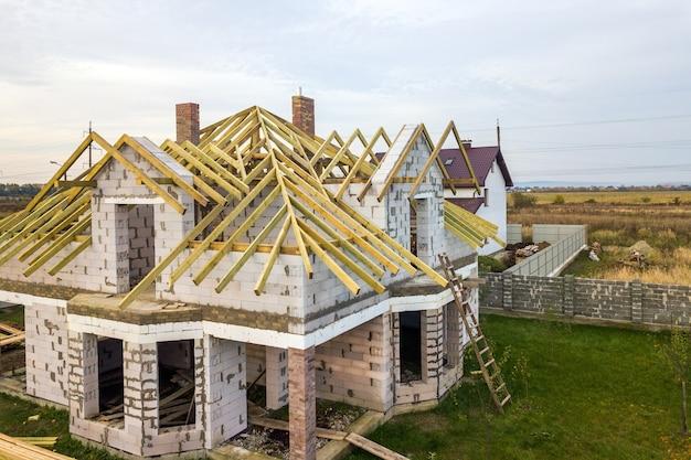 Widok z lotu ptaka na prywatny dom ze ścianami z cegły gazobetonowej i drewnianą ramą na przyszły dach