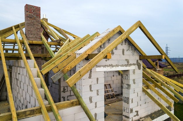 Widok z lotu ptaka na prywatny dom ze ścianami z cegły gazobetonowej i drewnianą ramą na przyszły dach.