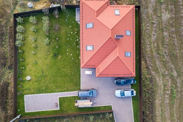 Widok z lotu ptaka na prywatny podmiejski dom z zaparkowanymi samochodami na podwórku.