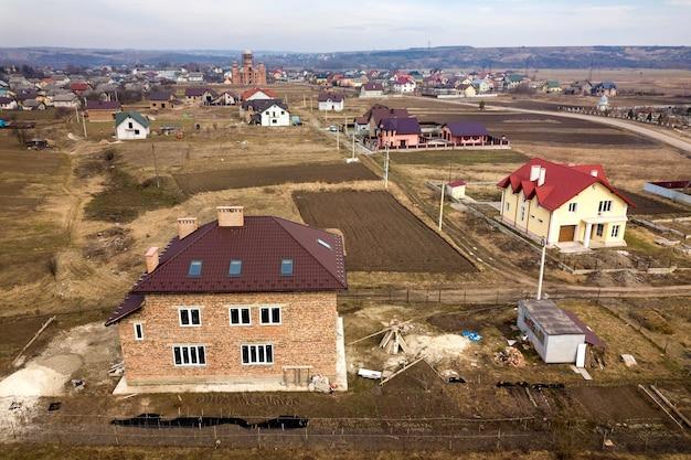 Widok z lotu ptaka na przedmieście z ładnymi domami i samochodami w słoneczny dzień.