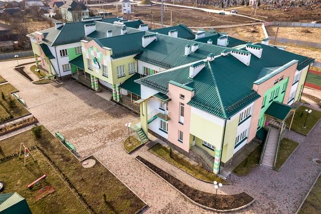 Widok z lotu ptaka na przedszkole lub nowoczesny zespół szkolny, zdobione dachy budynków