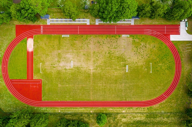 Widok z lotu ptaka na puste zielone boisko do piłki nożnej i czerwone bieżnie, tor wyścigowy na otwartym stadionie.