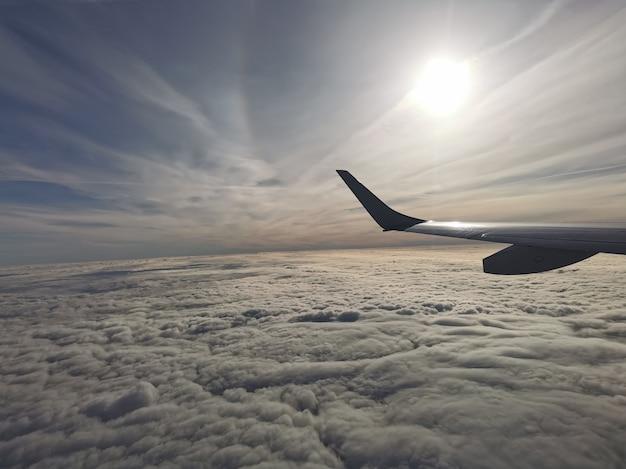 Widok z lotu ptaka na puszyste chmury ze słońcem pod skrzydłem samolotu