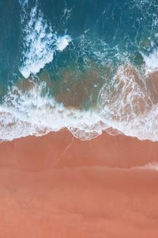 Widok z lotu ptaka na różową plażę i błękitną falę oceanu.