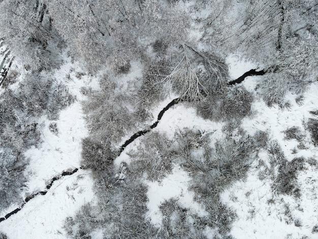 Widok z lotu ptaka na rzekę w zimowym lesie pokrytym śniegiem. fotografia dronów. rosyjski zimowy krajobraz. widok z góry