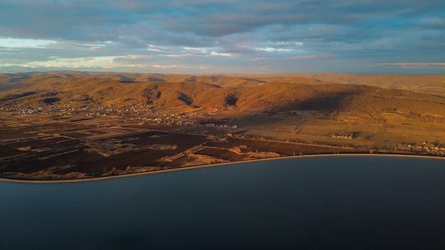 Widok z lotu ptaka na rzekę z żółtymi górami i budynkami pod zachmurzonym niebem