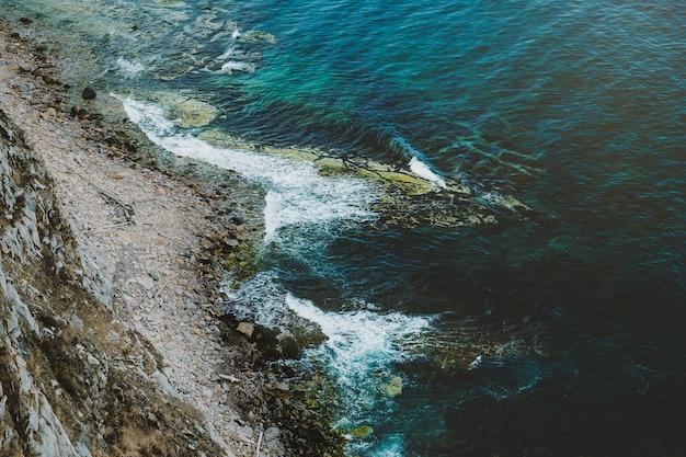 Widok z lotu ptaka na skaliste wybrzeże i turkusową wodę morską