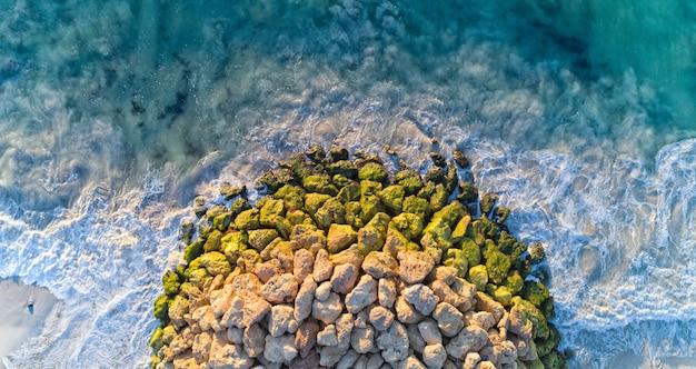Widok z lotu ptaka na skały na siebie otoczone falującym morzem w słońcu w ciągu dnia