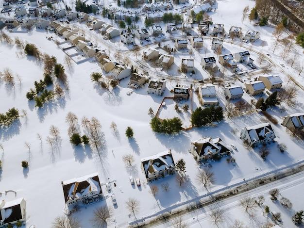 Widok z lotu ptaka na śnieg w tradycyjnych przedmieściach mieszkaniowych w śniegu na drzewach w zimie, widok na panoramę