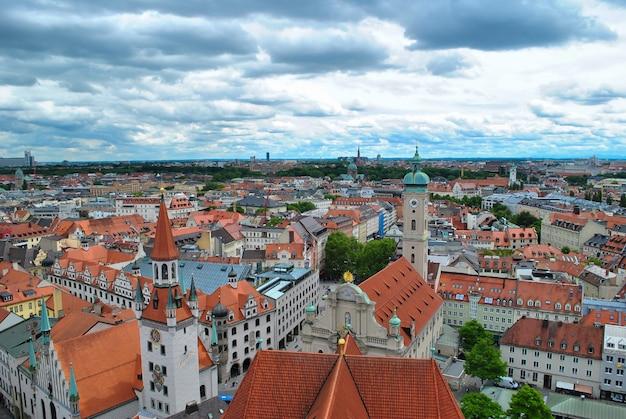 Widok z lotu ptaka na średniowieczne miasto z brązowymi dachami krytymi dachówką na tle błękitnego nieba