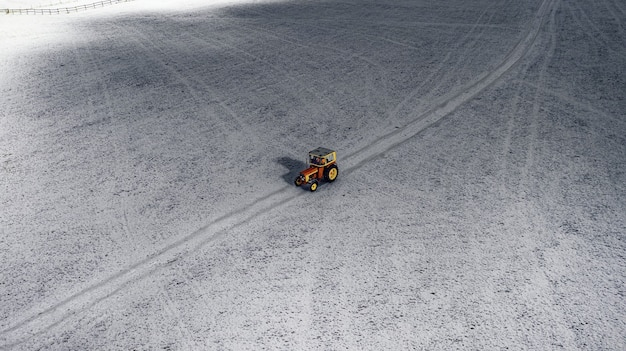 Widok z lotu ptaka na traktor na zaśnieżonym polu