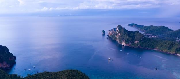 Widok z lotu ptaka na tropikalną wyspę ko phi phi i pasażerów łodzi w niebieskiej, czystej wodzie morskiej andamanów z góry, piękny w sezonie krabi, tajlandia