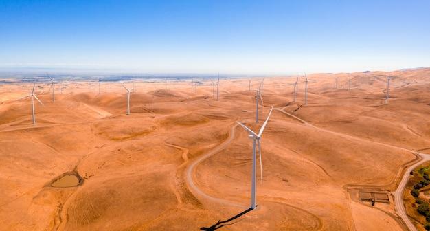 Widok z lotu ptaka na turbiny wiatrowe i krętą drogę na pięknym złotym górskim krajobrazie w kalifornii