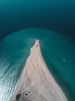 Widok z lotu ptaka na turkusową falę oceanu docierającą do linii brzegowej