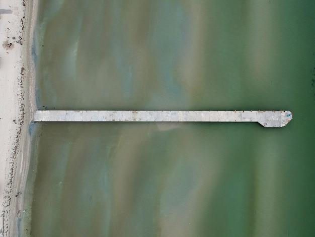 Widok z lotu ptaka na turkusową wodę z betonowym pomostem na jeziorze
