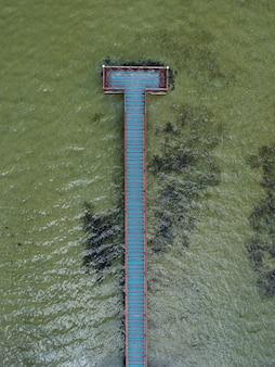 Widok z lotu ptaka na turkusową wodę z drewnianym pomostem na jeziorze
