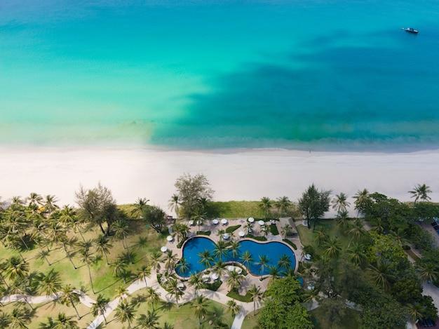 Widok z lotu ptaka na turkusowe morze i plażę z białym piaskiem, z dużym prywatnym basenem w roślinności