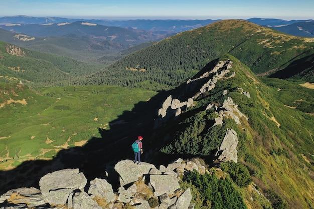 Widok z lotu ptaka na turystę z plecakiem relaks na szczycie góry i cieszenie się doliną