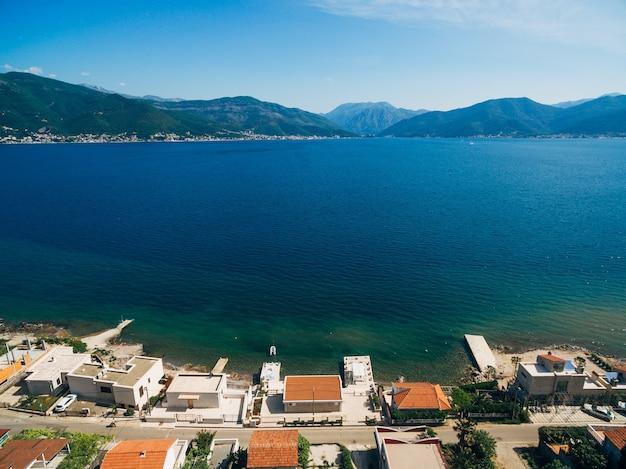 Widok z lotu ptaka na ulicę z domami na wybrzeżu zatoki kotorskiej w czarnogórze