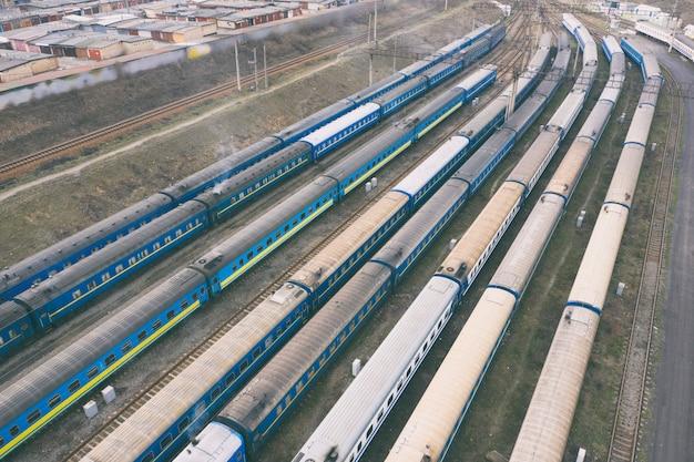 Widok z lotu ptaka na wielopasmowy węzeł kolejowy z pociągami, pasażerami i wagonami towarowymi. skład wagonu.