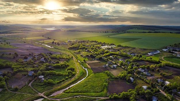 Widok z lotu ptaka na wieś w mołdawii o zachodzie słońca budynki mieszkalne wąska zieleń rzeczna