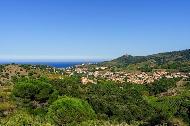 Widok z lotu ptaka na wioskę w środku doliny z widokiem na morze. colliure, francja