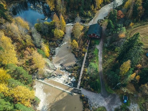 Widok z lotu ptaka na wodospad, bystrza i starożytny młyn. zdjęcie zrobione z drona. finlandia, pornainen.