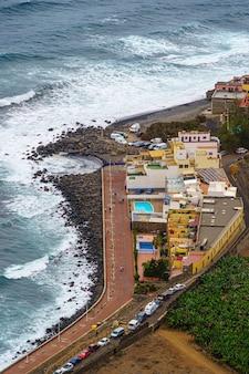 Widok z lotu ptaka na wybrzeże gran canarii z domami i falami na morzu. hiszpania, europa,