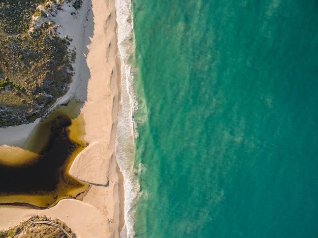 Widok z lotu ptaka na wybrzeże otoczone morzem w słońcu w dzień - fajne na tapetach