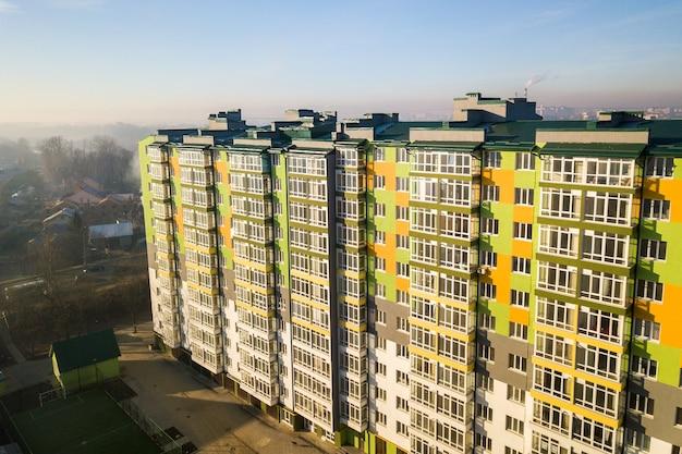 Widok z lotu ptaka na wysoki apartamentowiec z wieloma oknami i balkonami.