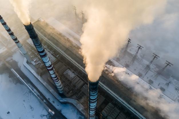 Widok z lotu ptaka na wysokie rury elektrowni węglowej z czarnym dymem poruszającym się w górę zanieczyszczającej atmosferę o zachodzie słońca.