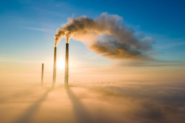 Widok z lotu ptaka na wysokie rury elektrowni węglowej z czarnym dymem poruszającym się w górę zanieczyszczającej atmosferę o zachodzie słońca