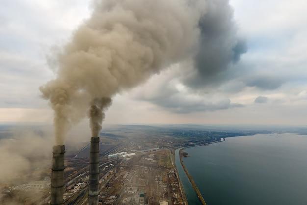 Widok z lotu ptaka na wysokie rury elektrowni węglowej z czarnym dymem unoszącym się w górę zanieczyszczającej atmosfery.