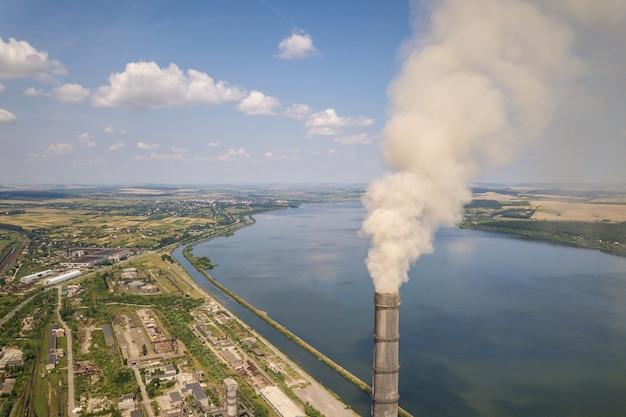 Widok z lotu ptaka na wysokie rury kominowe z szarym dymem z elektrowni węglowej. produkcja energii elektrycznej z paliw kopalnych.