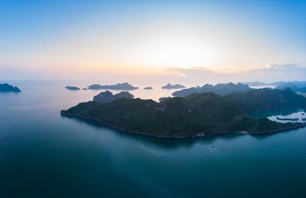 Widok z lotu ptaka na wyspę cat ba ha long bay, unikalne wapienne wyspy skalne i szczyty formacji krasowych na morzu, słynne miejsce turystyczne w wietnamie. malownicze błękitne niebo.