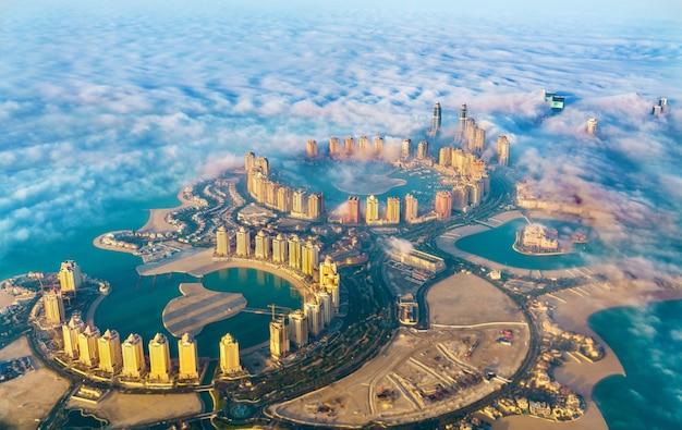 Widok z lotu ptaka na wyspę pearl-qatar w doha przez poranną mgłę - katar, zatoka perska