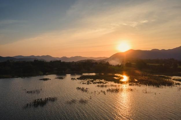 Widok z lotu ptaka na zachód słońca nad pasmem górskim i zbiornikiem na wsi w suphanburi