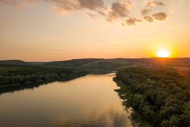 Widok z lotu ptaka na zachód słońca nad szeroką rzeką dniestr i odległymi skalistymi wzgórzami w rejonie bakoty, części parku narodowego