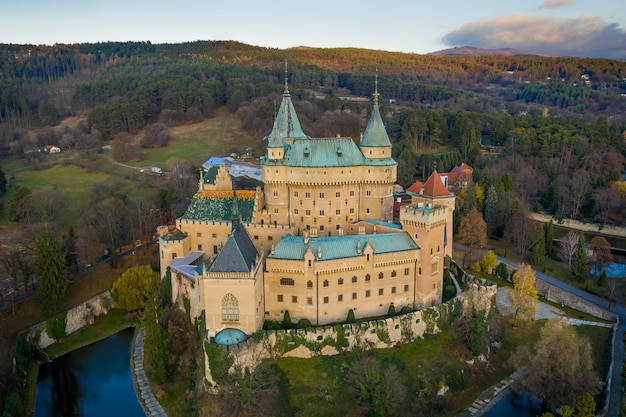 Widok z lotu ptaka na zamek bojnice na słowacji strzeżony fosą i otoczony lasem.